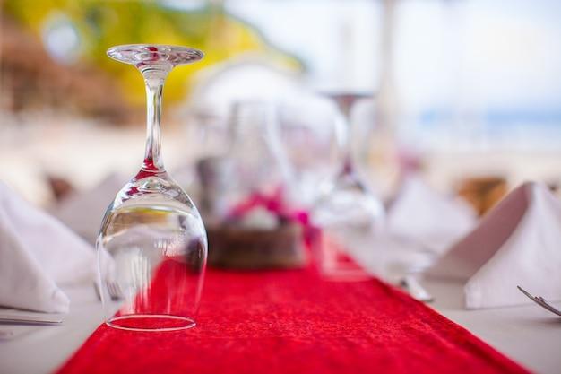 夕暮れ時の宴会のセットテーブルの上のワイングラスのクローズアップ Premium写真