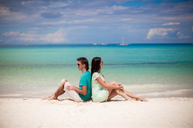砂浜でお互いを楽しんでいる若いカップル Premium写真
