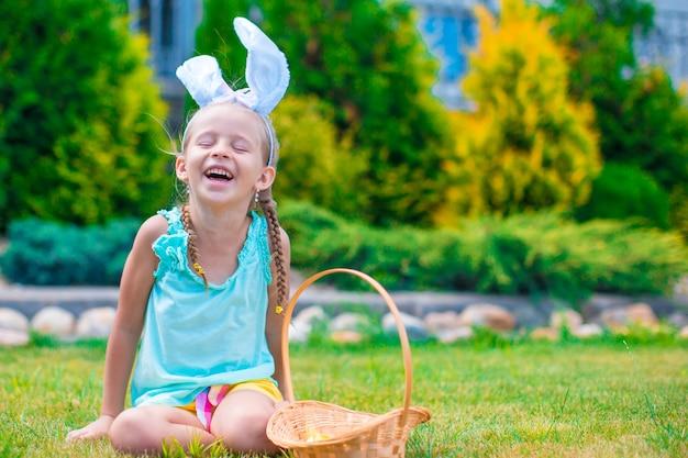 屋外の小さな女の子とハッピーイースター Premium写真