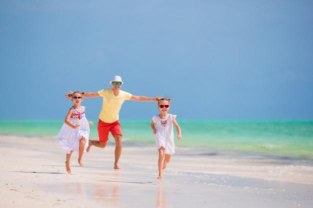 楽しんで熱帯のビーチで幸せな家族 Premium写真