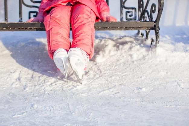 冬のアイススケートリンクに立っている小さなスケーターの足 Premium写真