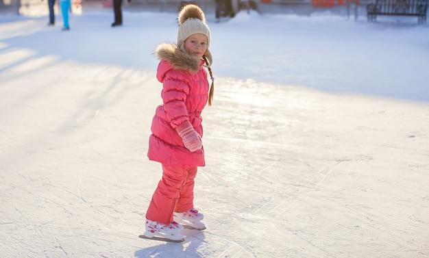 アイススケートリンクでスケートを楽しんでいるかわいい女の子 Premium写真
