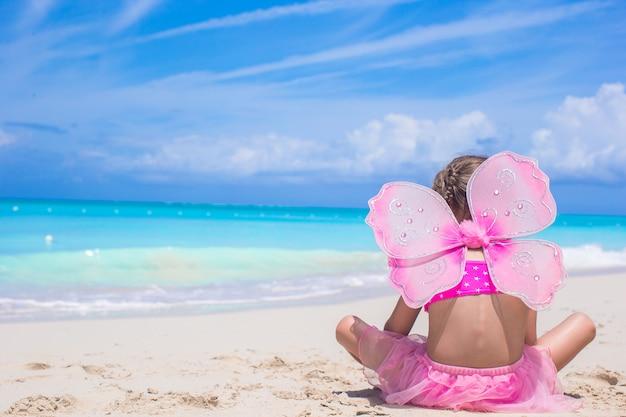 ビーチでの休暇に蝶の羽とかわいい女の子 Premium写真