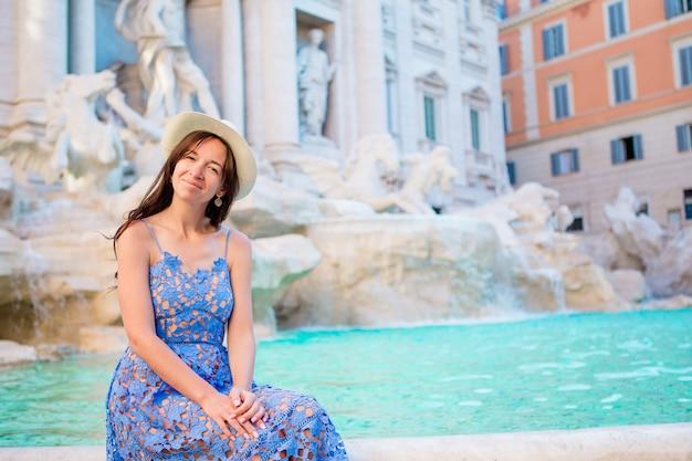 市内地図と噴水フォンタナディトレビ近くの美しい少女 Premium写真