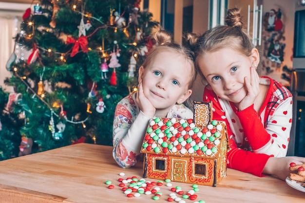 飾られたリビングルームの暖炉のそばでクリスマスのジンジャーブレッドの家を作る小さな女の子。 Premium写真