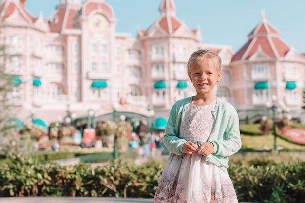 おとぎ話のディズニーランドパークでシンデレラドレスの愛らしい少女 Premium写真