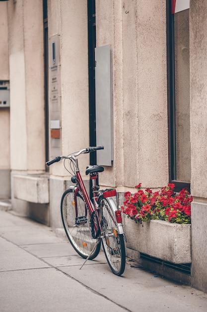 ウィーンの花と古い壁の近くの自転車で美しい都市景観 Premium写真