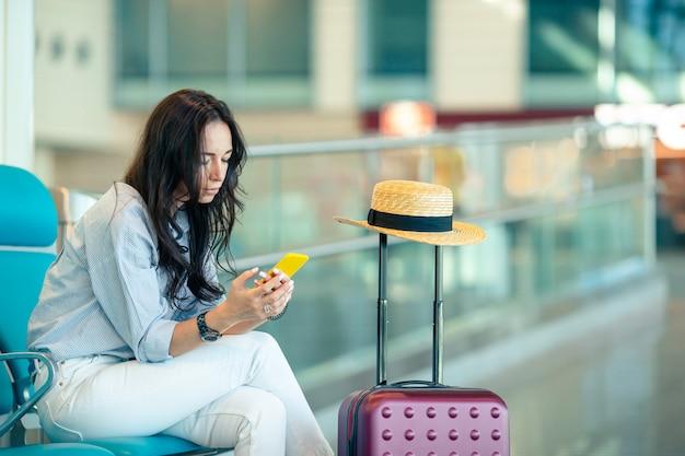 飛行機を待っている空港ラウンジでコーヒーを持つ若い女性 Premium写真