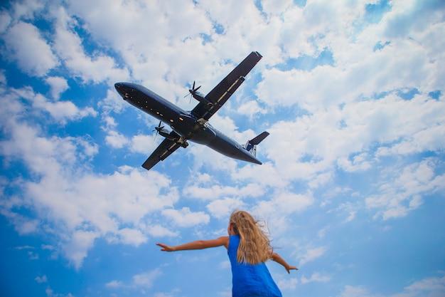 空を見て、彼女の上に飛行機を飛んでかわいい子女の子 Premium写真