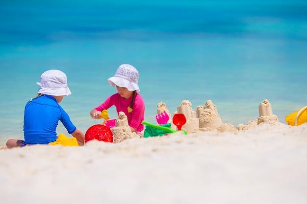 熱帯の休暇中にビーチおもちゃで遊ぶ女の子 Premium写真