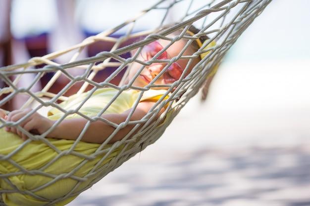 ハンモックでリラックスした熱帯の休暇のかわいい女の子 Premium写真