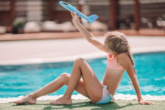 屋外プールの近くで楽しんで美しい少女 Premium写真