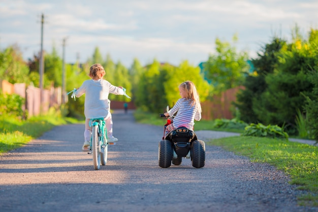 Счастливые маленькие девочки на велосипедах на открытом воздухе в парке Premium Фотографии