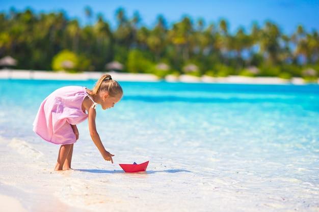 ターコイズブルーの海で折り紙の船で遊ぶ愛らしい少女 Premium写真