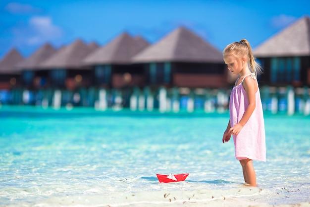 ターコイズブルーの海で紙の船で遊ぶ愛らしい少女 Premium写真