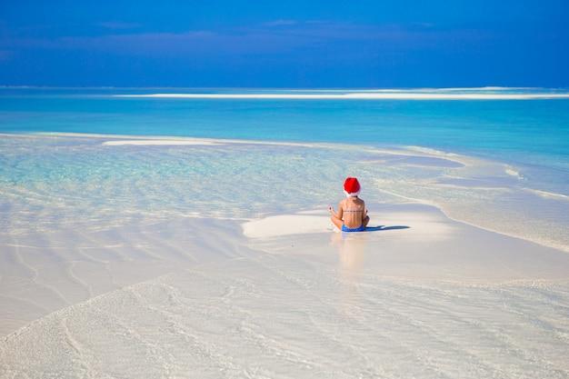休暇中にビーチでサンタ帽子でのかわいい女の子 Premium写真