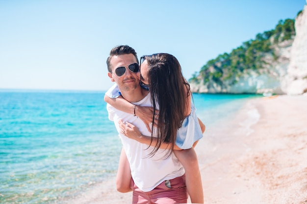 Молодая пара на белом пляже во время летних каникул. Premium Фотографии