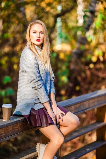 Осень концепция - красивая женщина пьет кофе в осеннем парке под осенней листвой Premium Фотографии