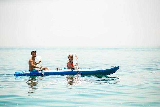 一緒に海でカヤックをするスポーティな魅力的な家族 Premium写真