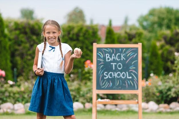 Счастливый маленькая школьница с доске на открытом воздухе Premium Фотографии