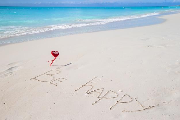 Будь счастлив написан на песчаном тропическом пляже Premium Фотографии