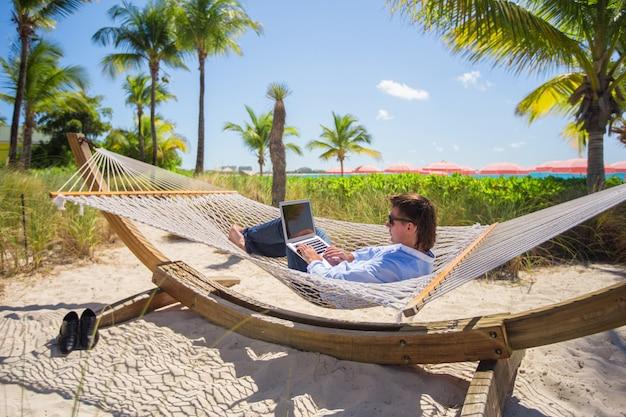 熱帯のビーチでハンモックでラップトップに取り組んでいる若い男 Premium写真