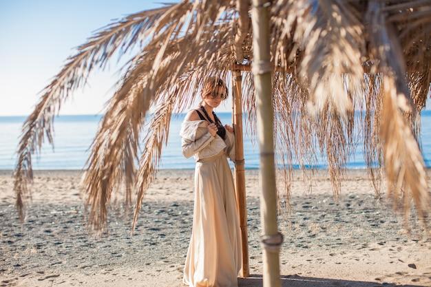 ビーチで美しいドレスの愛らしい若い女性 Premium写真
