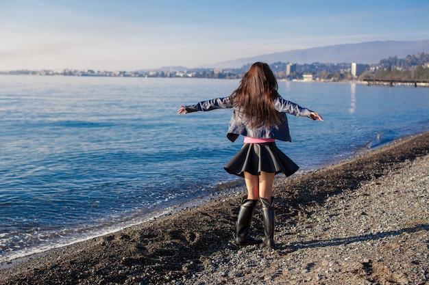 美しい若い女性は一人で冬の晴れた日のビーチでリラックスします。 Premium写真