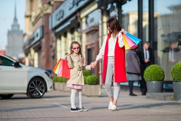 屋外でのショッピングで幸せな家族。母と娘は買い物で買い物をし、屋外の通りを歩いて楽しんでいます。 Premium写真