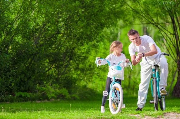 若い父親と夏の暖かい日に自転車に乗る少女。アクティブな若い家族が自転車に乗る Premium写真
