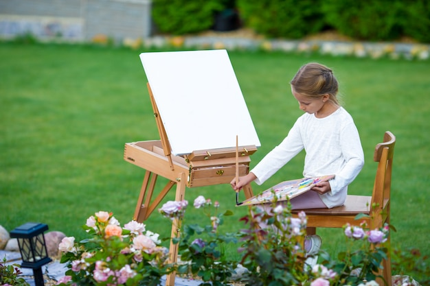 屋外のイーゼルに絵を描くのかわいい女の子。小さな芸術家は彼女の趣味に熱心です。 Premium写真