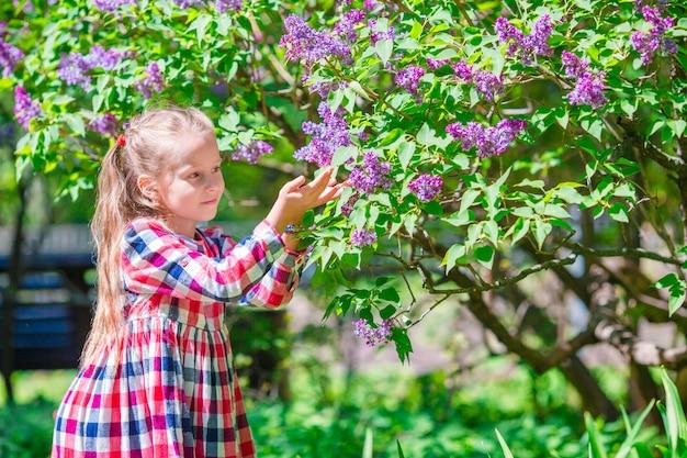 屋外の色とりどりの花の臭いがする愛らしい少女 Premium写真