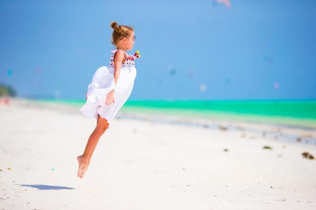 Прелестная маленькая девочка на пляже во время летних каникулов. милый парень с удовольствием прыгает и наслаждается пляжным отдыхом Premium Фотографии
