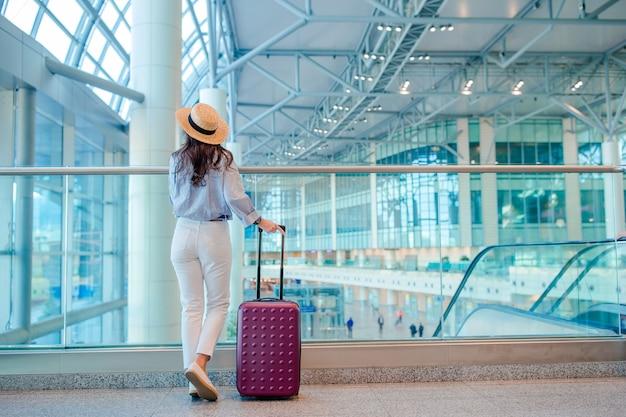 国際空港で荷物を持つ帽子の若い女性。 Premium写真