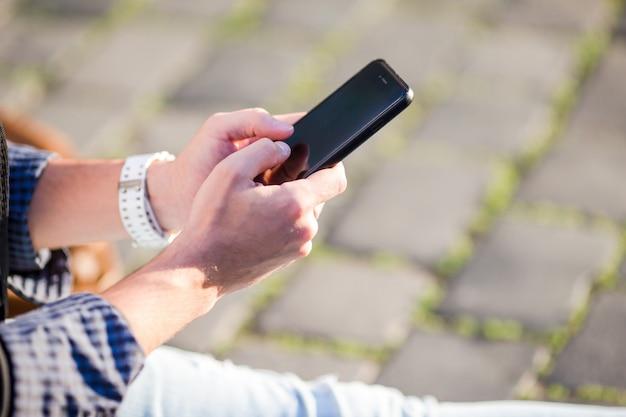 男性の手のクローズアップは、路上で屋外で携帯電話を保持しています。モバイルスマートフォンを使用している人。 Premium写真