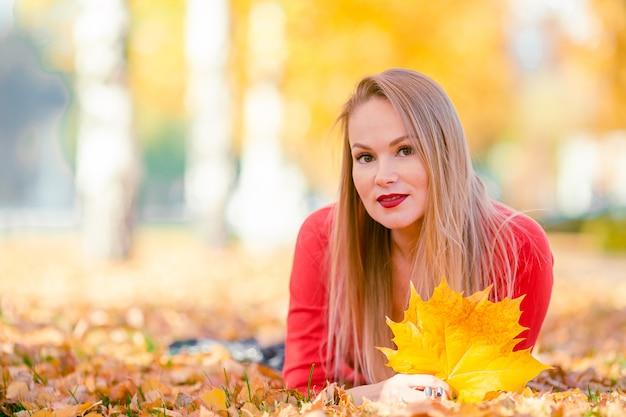 秋の紅葉の下で秋の公園でコーヒーを飲みながら美しい女性 Premium写真