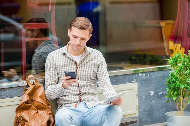 屋外路上で携帯電話を抱きかかえた。モバイルスマートフォンを使用している人。 Premium写真