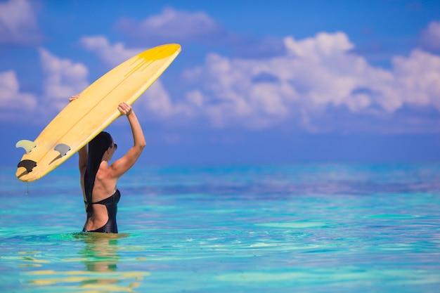 黄色のサーフボードと白いビーチで幸せな格好の良いサーフ女性 Premium写真