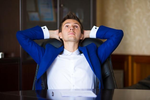 Деловой человек отдыхает в кресле в офисе Premium Фотографии