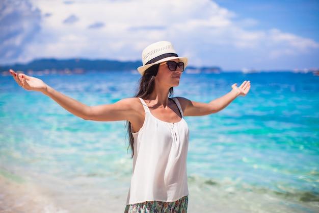 白い熱帯のビーチで休日を楽しんでいる若い美しい女性 Premium写真