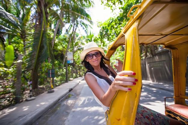 アジアの国でオープンタクシーの若い女性 Premium写真
