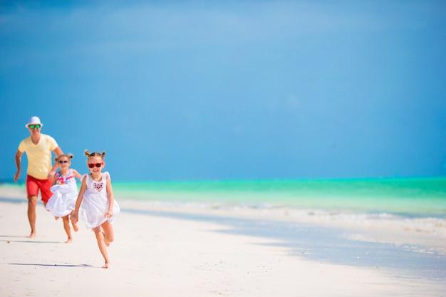ビーチで夏休みを楽しんでいる若い家族 Premium写真