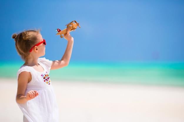 ビーチでの休暇中におもちゃの飛行機との幸せな女の子 Premium写真