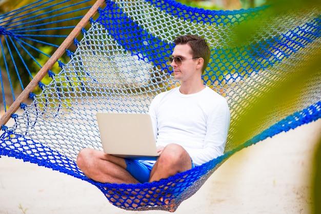 熱帯の休暇のハンモックでラップトップを持つ若者 Premium写真