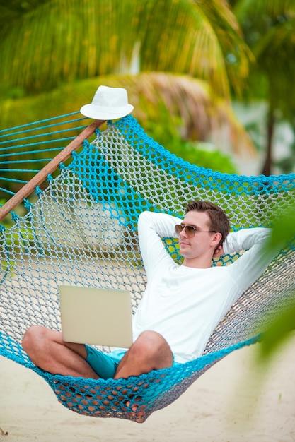 Молодой человек отдохнуть в гамаке на пляже тропический отдых Premium Фотографии