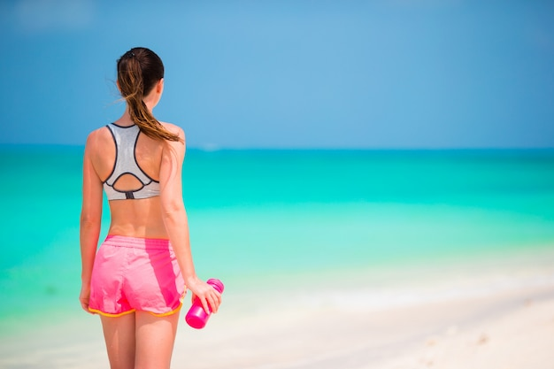 白いビーチに水のボトルとフィットの若い女の子 Premium写真