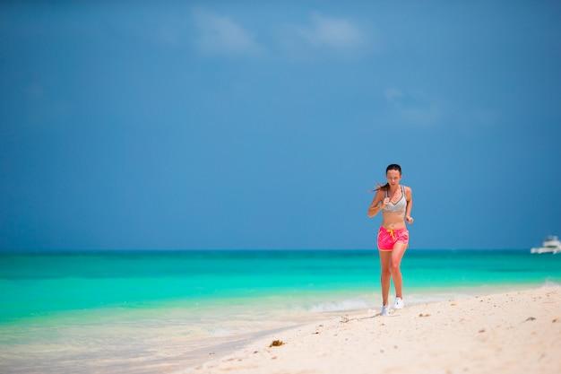 彼女のスポーツウェアで熱帯のビーチに沿って実行しているスポーツの若い女性に合う Premium写真