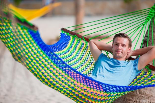 Молодой человек отдохнуть в гамаке Premium Фотографии
