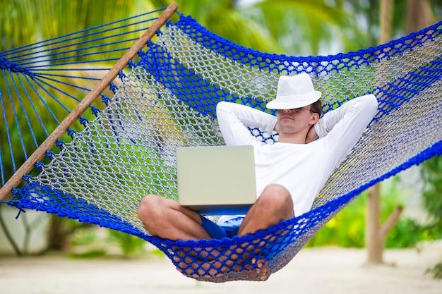 Молодой человек с ноутбуком в гамаке на белом пляже Premium Фотографии