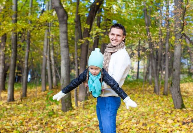 Счастливый папа и маленькая дочь с удовольствием в парке в солнечный осенний день Premium Фотографии